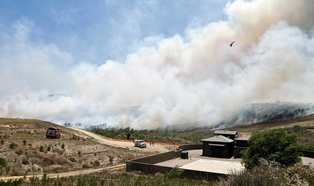 . Smoke rises from a canyon where a wild fire is burning Tuesday, May 13, 2014, in San Diego.   Wildfires forced the evacuation of 20,000 people as a high-pressure system brought unseasonable heat and gusty winds to a parched state that should be in the middle of its rainy season. (AP Photo)
