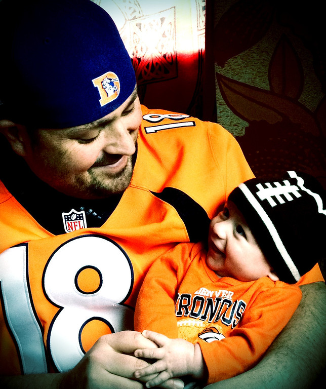. Dad and his 4 month old son getting ready to watch their first playoff game together last Sunday. Baby was born the night before the regular season started.  photo by Jaime Hohl