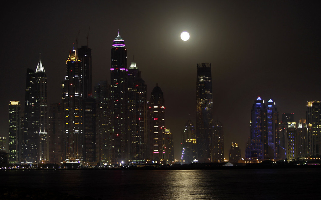. A super moon is seen behind the Marina district towers in Dubai, United Arab Emirates on Sunday, June 23, 2013. (AP Photo/Kamran Jebreili)
