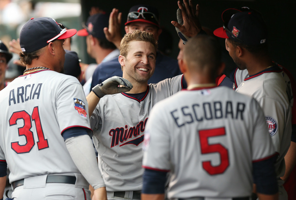 . Minnesota Twins\' Brian Dozier, center, is congratulated by teammates Oswaldo Arcia, left, and Eduardo Escobar after Dozier\'s three-run home run against the Colorado Rockies in the ninth inning of the Twins\' 13-5 victory in an interleague baseball game in Denver on Sunday, July 13, 2014. (AP Photo/David Zalubowski)