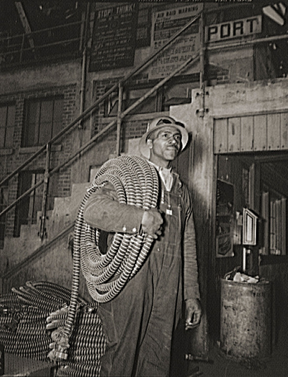 . Baltimore, Maryland. Building the SS Frederick Douglass. More than 6,000 Negro shipyard workers were employed at the Bethlehem-Fairfield shipyards where the Liberty ship was rushed to completion. The noted orator and abolitionist worked as a ship caulker in the vicinity of this yard before he escaped from slavery. James Bibons, soldier in the battle of production, carrying insulated electric cables for engine room. 1943 May. Roger Smith, photographer. Library of Congress