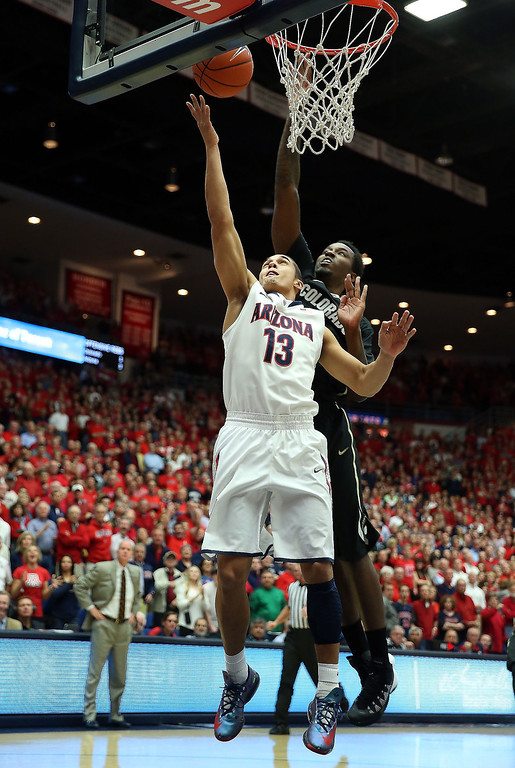 . Nick Johnson #13 of the Arizona Wildcats lays up a shot past Wesley Gordon #1 of the Colorado Buffaloes during the first half of the college basketball game at McKale Center on January 23, 2014 in Tucson, Arizona.  (Photo by Christian Petersen/Getty Images)