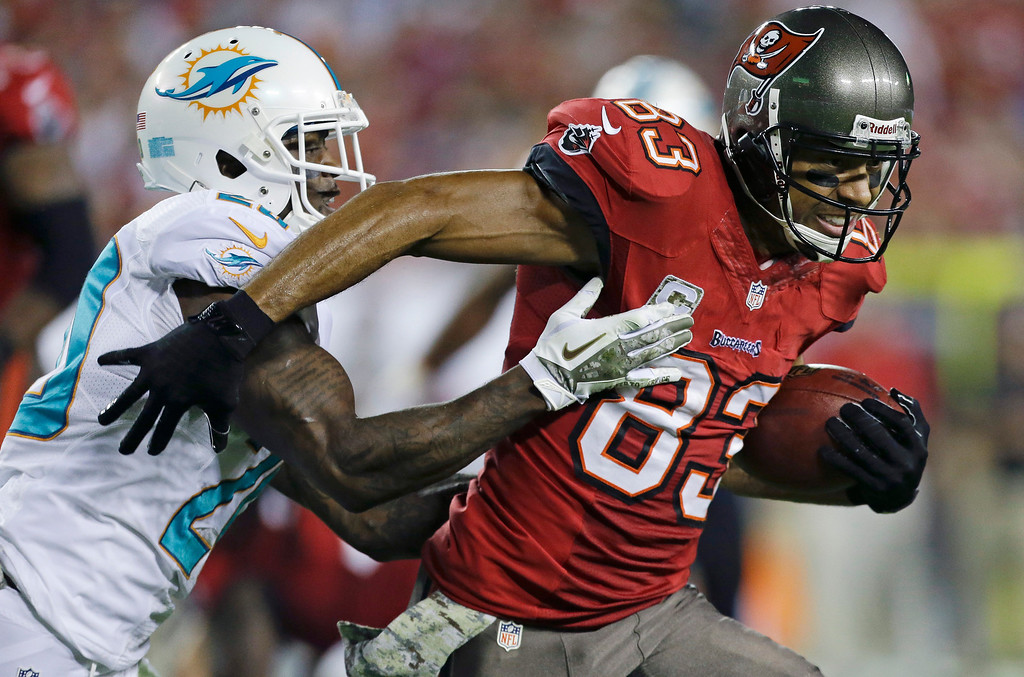 . Tampa Bay Buccaneers wide receiver Vincent Jackson (83) runs for yardage after a reception as he is tackled by Miami Dolphins free safety Reshad Jones, left, during the first half of an NFL football game in Tampa, Fla., Monday, Nov. 11, 2013.(AP Photo/John Raoux)