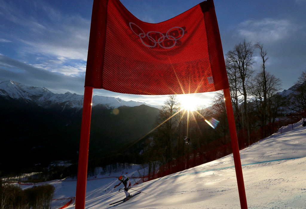. A skier inspects the men\'s downhill ski course at dawn ahead of the men\'s supercombined at the Sochi 2014 Winter Olympics, Friday, Feb. 14, 2014, in Krasnaya Polyana, Russia. (AP Photo/Luca Bruno)