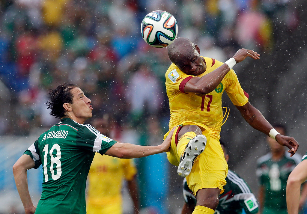 . Cameroon\'s Stephane Mbia (17) heads the ball past Mexico\'s Andres Guardado during first half of the group A World Cup soccer match between Mexico and Cameroon in the Arena das Dunas in Natal, Brazil, Friday, June 13, 2014.  (AP Photo/Petr David Josek)