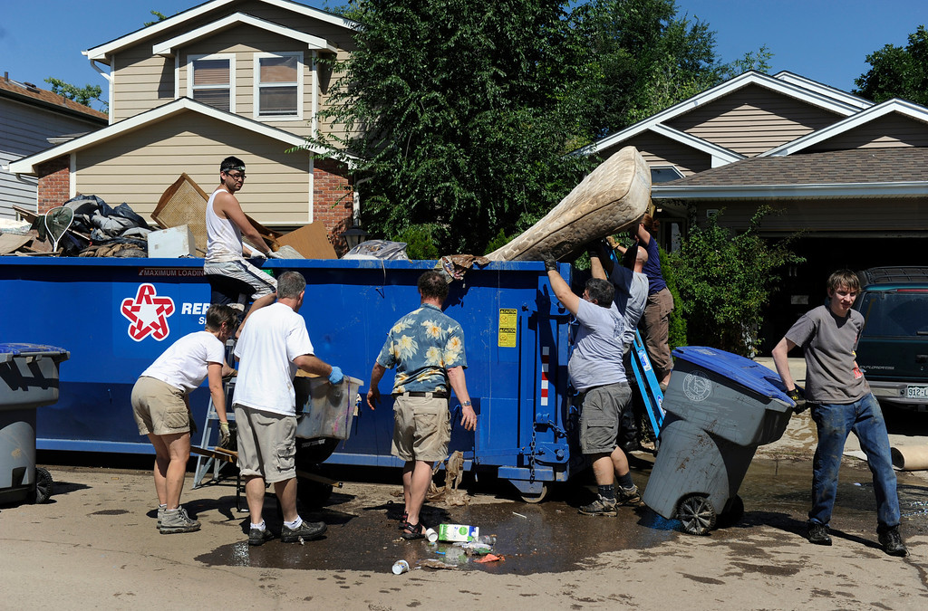 . LONGMONT, CO - Sept. 17: The city placed a large dumpster in the street so residents could begin to get rid of debris. Residents along Wade Road just south of Twin Peaks Golf Course begin the grim job of clean up from flood waters that submerged their neighborhood this past week. (Photo By Kathryn Scott Osler/The Denver Post)