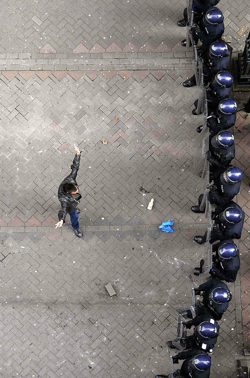 . A lone protester faces a line of riot police during skirmishes in central Edinburgh July 4, 2005. Riot police used mounted and baton charges to quell disturbance and contain protestors who are in the city to protest during the G8 summit in Gleneagles. Jeff J Mitchell UK / Reuters