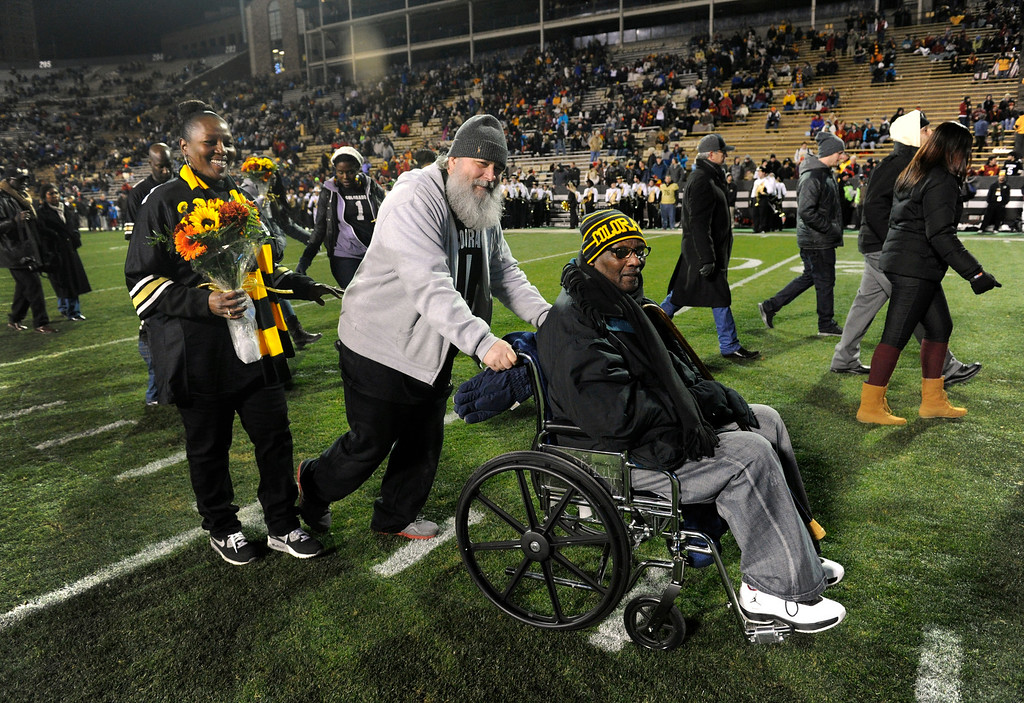 . BOULDER, CO - NOVEMBER 23: After the end of the on-field, pre-game Senior Day ceremony, Derrick Webb\'s mother, Felicia Morris; his stepfather, Billy Morris, and his grandfather, Harold Scott head off the field before the start the game against the Southern California Trojans at Folsom Field in mid-November. It is senior day and the last home game of the season, and each senior player is recognized and greeted by family and friends on the field. Despite feeling under the weather and freezing temperatures, Webb\'s grandfather Harold Scott, (in the wheelchair) made the trip to see Derrick play in his final home game. Scott is given assistance by Felicia\'s husband, Billy. (Photo by Kathryn Scott Osler/The Denver Post)