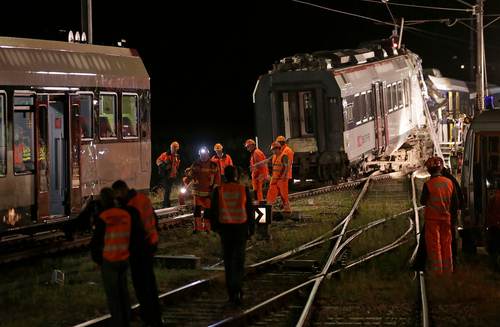 . Swiss Federal Railways (SBB) staff remove carriages at the site of a head-on collision between two trains near Granges-pres-Marnand, near Payerne in western Switzerland July 29, 2013. The two trains collided head-on in Switzerland on Monday evening, injuring about 35 people, five seriously, police said. The driver of one of the trains was still unaccounted for and thought to be inside the wreckage, at Granges-pres-Marnand in the canton of Vaud, police spokesman Jean-Christophe Sauterel said. REUTERS/Denis Balibouse