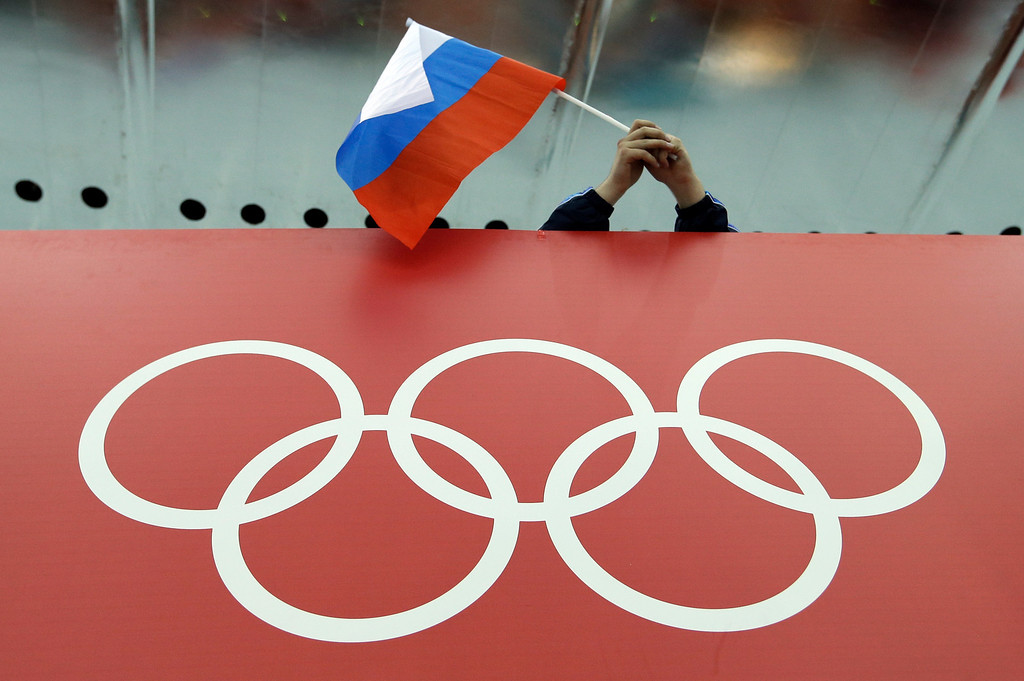 . A Russian skating fan holds the country\'s national flag over the Olympic rings before the start of the men\'s 10,000-meter speedskating race at Adler Arena Skating Center during the 2014 Winter Olympics in Sochi, Russia, Tuesday, Feb. 18, 2014.(AP Photo/David J. Phillip )