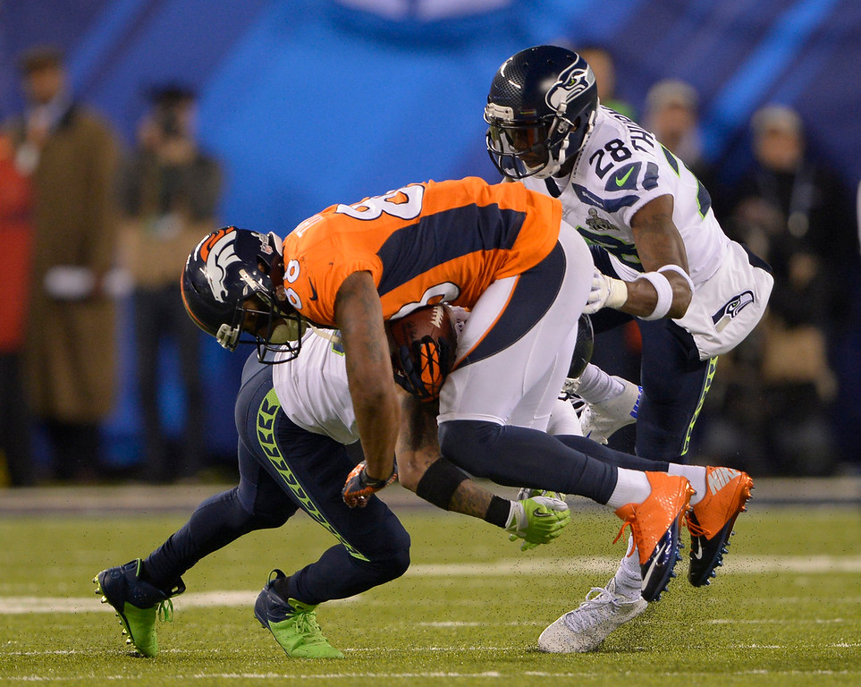. Denver Broncos wide receiver Demaryius Thomas (88) gets tiled during the fourth quarter. The Denver Broncos vs the Seattle Seahawks in Super Bowl XLVIII at MetLife Stadium in East Rutherford, New Jersey Sunday, February 2, 2014. (Photo by Joe Amon/The Denver Post)