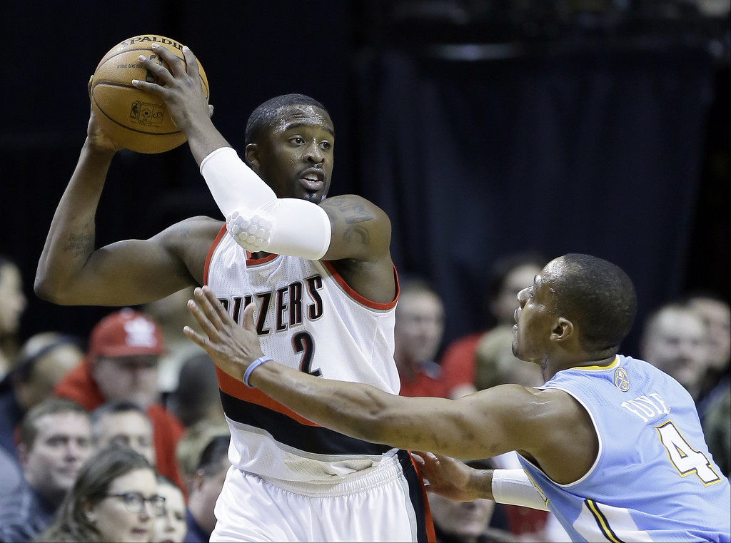 . Portland Trail Blazers guard Wesley Matthews, left, looks to pass against Denver Nuggets guard Randy Foye during the first half of an NBA basketball game in Portland, Ore., Thursday, Jan. 23, 2014. (AP Photo/Don Ryan)