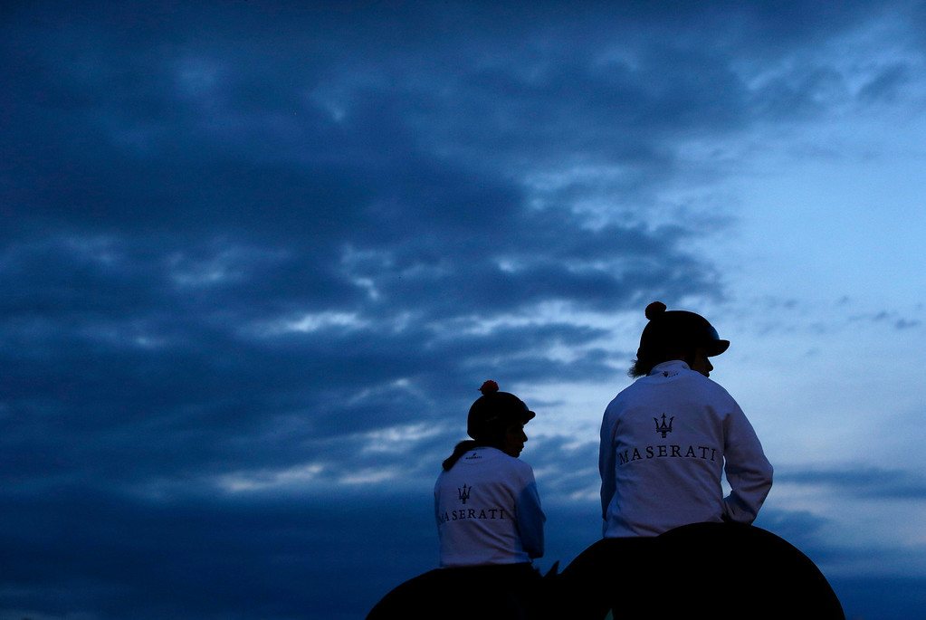 . Exercise rider Jennifer Patterson, right, sits on Kentucky Derby winner Orb alongside escort Anna Martinovsky as they prepare for a workout at Pimlico Race Course in Baltimore, Saturday, May 18, 2013, on the morning of the 138th running of the Preakness Stakes horse race. (AP Photo/Patrick Semansky)