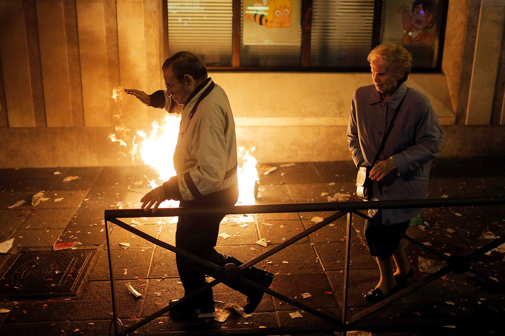 . A elderly couple pass by burning trash during a demonstration against layoffs of street cleaners and garbage collectors in Madrid, Spain, Monday, Nov. 4, 2013. Trash collectors in Madrid have started bonfires and set off firecrackers during a noisy protest in one of the Spanish capitalís main squares as they prepare to start an open-ended strike. (AP Photo/Andres Kudacki)