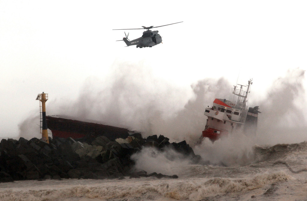 . A military helicopter flies over a Spanish cargo ship that slammed into a jetty in choppy Atlantic Ocean waters off Anglet, southwestern France, Wednesday, Feb. 5, 2014.   (AP Photo/Bob Edme)