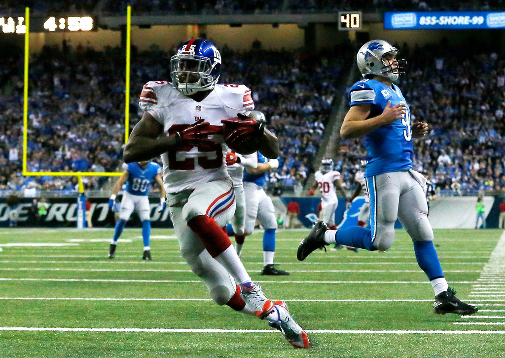 . New York Giants\' Will Hill (25) runs into the end zone for a touchdown after intercepting Detroit Lions quarterback Matthew Stafford (9), background, during the fourth quarter of an NFL football game in Detroit, Sunday, Dec. 22, 2013. (AP Photo/Paul Sancya)