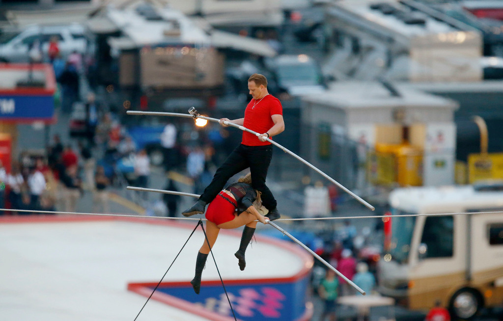 . Nik Wallenda steps over his sister Lijana Wallenda as they perform on a tightrope before the NASCAR Sprint Cup Series auto race at Charlotte Motor Speedway in Concord, N.C., Saturday, Oct. 12, 2013. (AP Photo/Chris Keane)