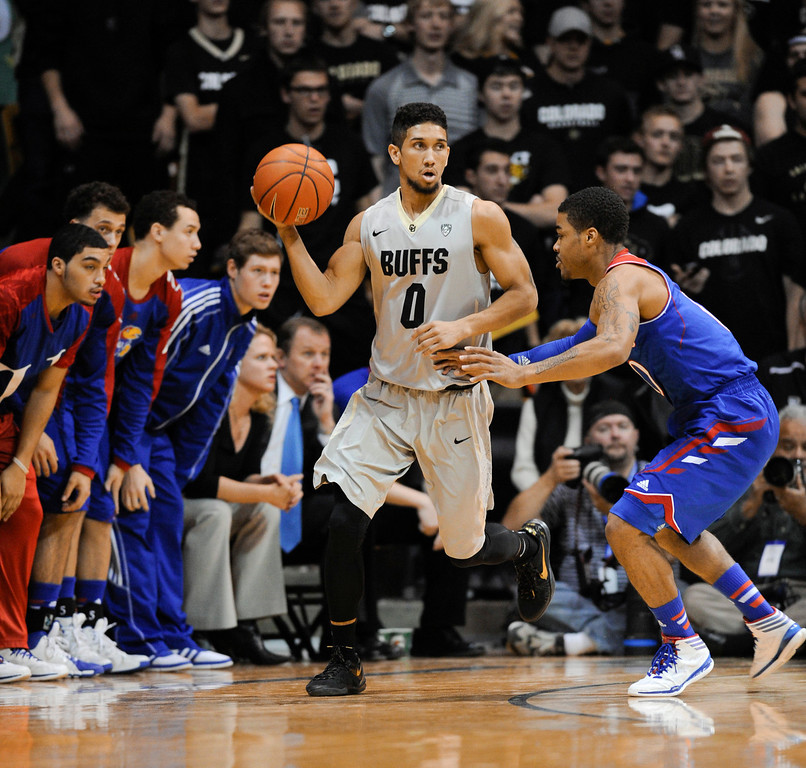 . Colorado University point guard, Askia Booker, left, looks for an open man against Kansas guard, Frank Mason in the first half of play at the Coors Events Center in Boulder Colorado Saturday afternoon, December 07, 2013. (Photo By Andy Cross/The Denver Post)