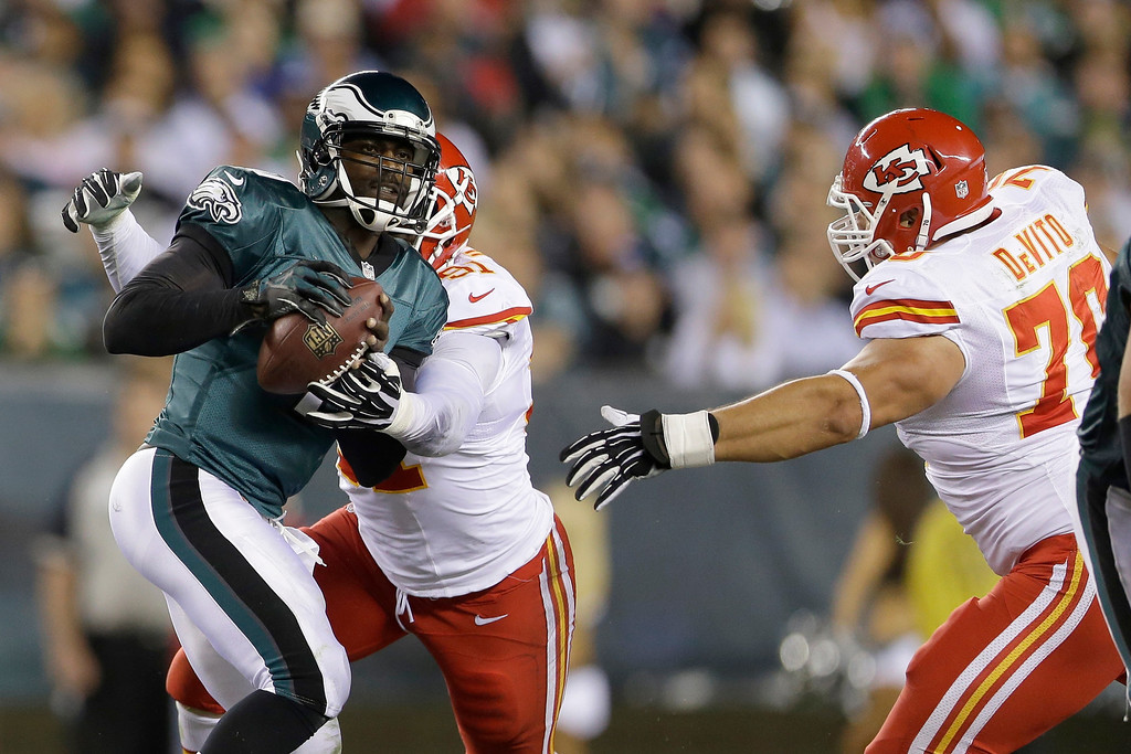 . Philadelphia Eagles\' Michael Vick, left, is cornered by Kansas City Chiefs\' Tamba Hali and Mike DeVito during the first half of an NFL football game, Thursday, Sept. 19, 2013, in Philadelphia. (AP Photo/Matt Rourke)