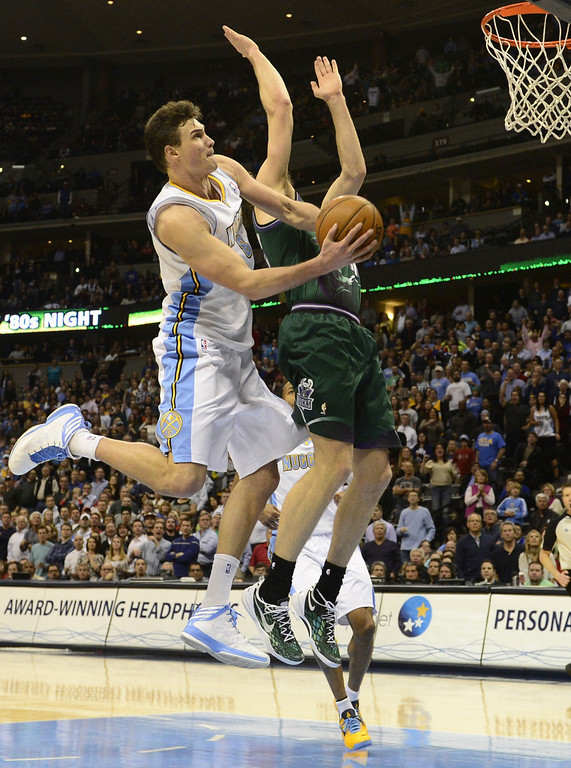 . DENVER, CO - FEBRUARY 5: Danilo Gallinari Denver Nuggets (8) makes a circus shot while being fouled by Mike Dunleavy Milwaukee Bucks (17) during the second half of action. The Denver Nuggets defeat the Milwaukee Bucks 112-104 in NBA action at the Pepsi Center. (Photo By AAron Ontiveroz/The Denver Post)