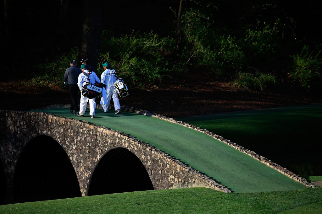 . Mark O\'Meara of the United States and Hideki Matsuyama of Japan walk with their caddies over the Hogan Bridge during a practice round prior to the start of the 2014 Masters Tournament at Augusta National Golf Club on April 9, 2014 in Augusta, Georgia.  (Photo by Rob Carr/Getty Images)