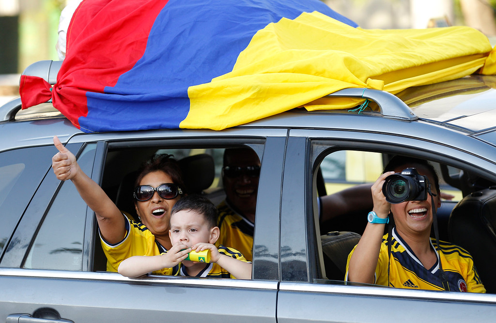 . Colombian fans drive past of the Maracana stadium with the Colombian national flag tied to their car, in Rio de Janeiro, Brazil, Wednesday, June 11, 2014. The World Cup soccer tournament starts Thursday. (AP Photo/Leo Correa)