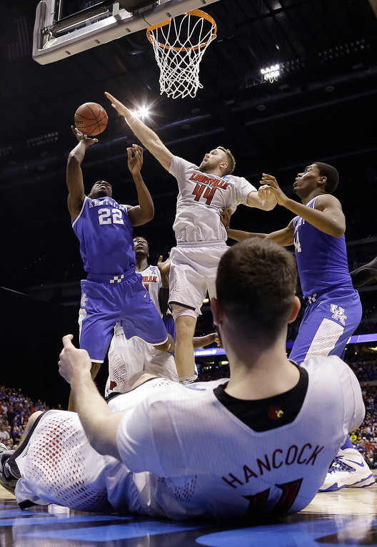 . Kentucky\'s Alex Poythress (22) tries to shoot past Louisville\'s Stephan Van Treese (44) as Luke Hancock lays on the ground during the second half of an NCAA Midwest Regional semifinal college basketball tournament game Saturday, March 29, 2014, in Indianapolis. (AP Photo/David J. Phillip)