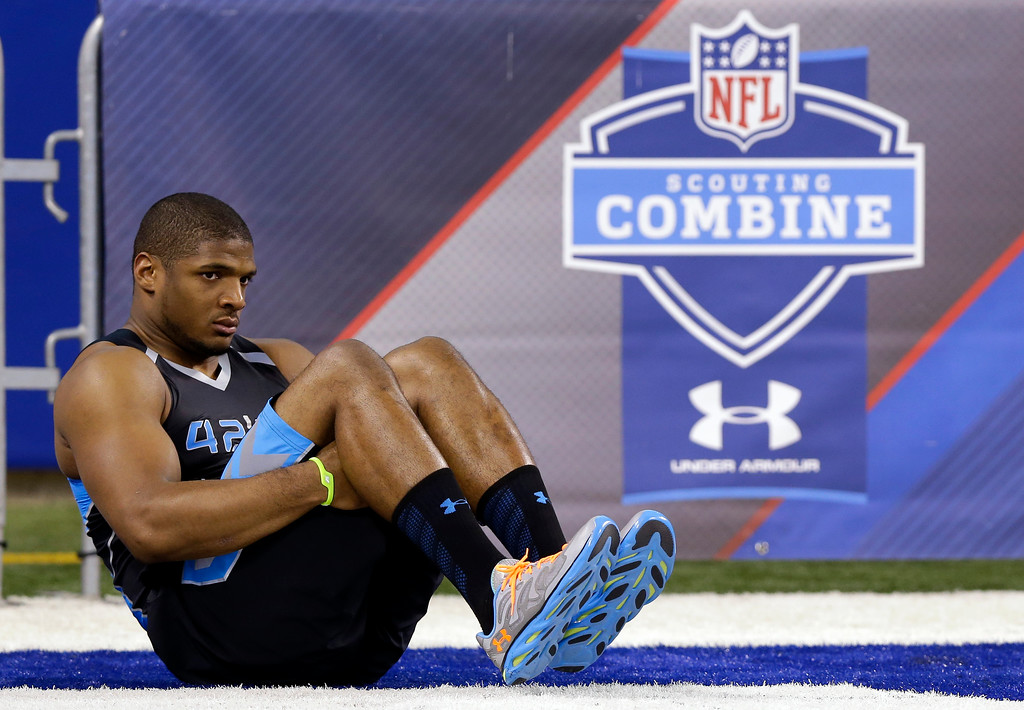 . Missouri defensive lineman Michael Sam stretches before drills at the NFL football scouting combine in Indianapolis, Monday, Feb. 24, 2014. (AP Photo/Michael Conroy)