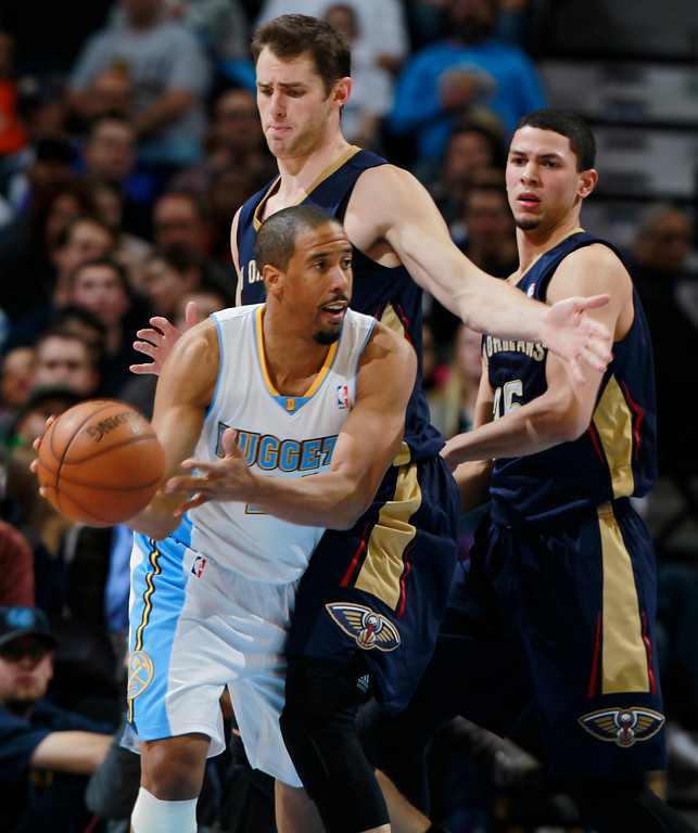 . Denver Nuggets guard Andre Miller, front, passes the ball as New Orleans Pelicans forward Jason Smith, center, and guard Austin Rivers cover in the third quarter of the Nuggets\' 102-93 victory in an NBA basketball game in Denver on Sunday, Dec. 15, 2013. (AP Photo/David Zalubowski)