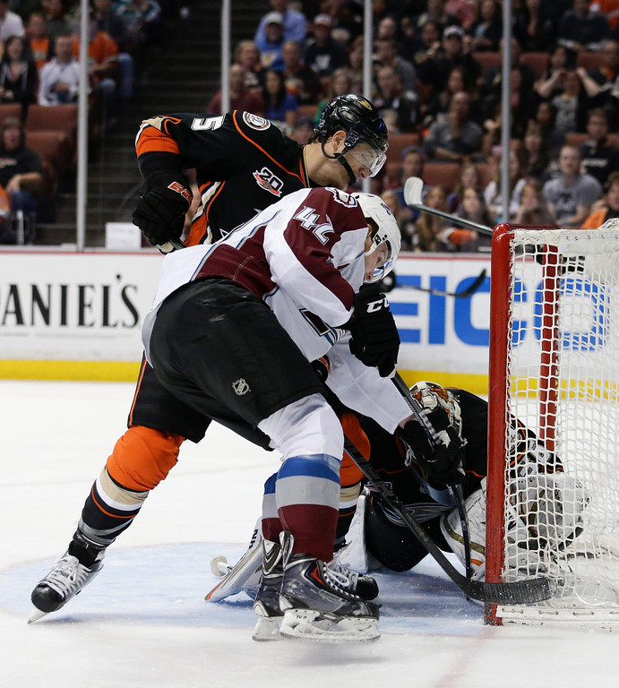 . Colorado Avalanche\'s Brad Malone, center, scores against Anaheim Ducks goalie John Gibson, right, as he is defended by Anaheim Ducks\' Luca Sbisa, of Italy, during the first period of an NHL hockey game on Sunday, April 13, 2014, in Anaheim, Calif. (AP Photo/Jae C. Hong)