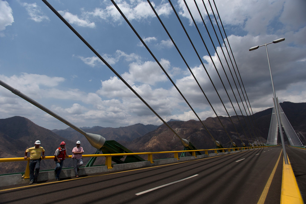 . In this June 11, 2013 photo, workers stand at the recently completed bridge called the Baluarte near Concordia, Mexico. A new Durango-Mazatlan highway will pass through colonial Concordia, founded in 1565 by the Spaniards as a way station between the coast and the gold mines. Government officials say the new road will bring legitimate economy to a troubled area. Locals say it may improve access, or take what little honest business they had as trucks and buses bypass towns altogether. (AP Photo/Dario Lopez-Mills)