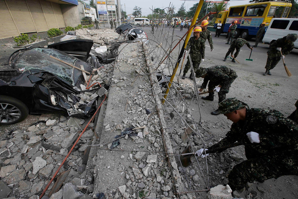 . Soldiers remove the debris that fell over cars following a 7.2-magnitude earthquake that hit Cebu city in central Philippines Tuesday, Oct. 15, 2013. (AP Photo/Bullit Marquez)