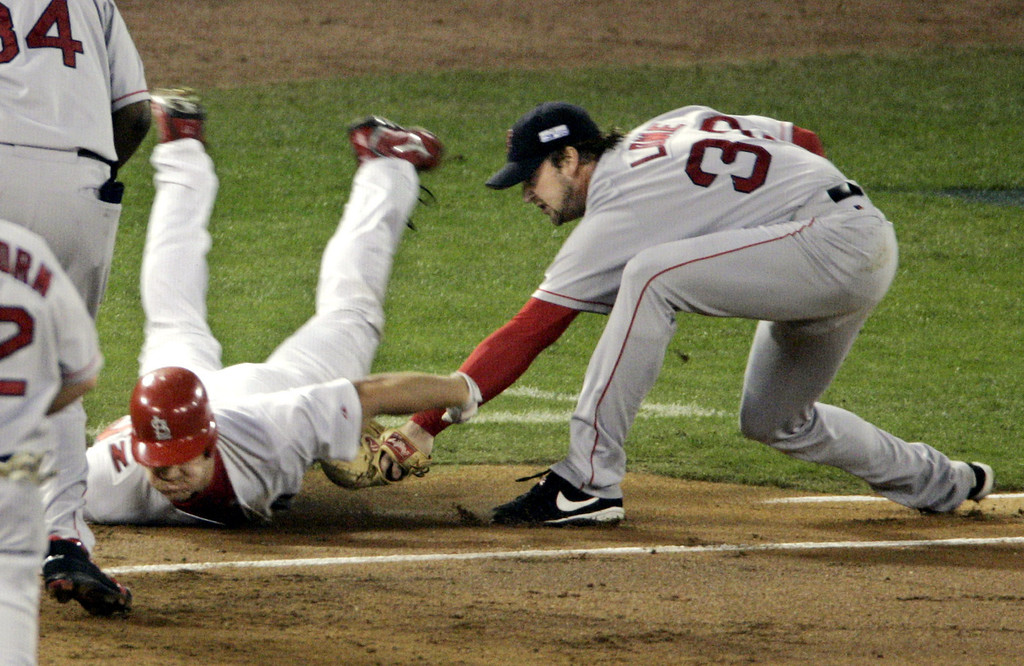 . Boston Red Sox pitcher Derek Lowe, right, puts the tag on St. Louis Cardinals Scott Rolen as Rolen tries to dive to first base on his chopper down the first base line during the first inning of Game 4 of the World Series at Busch Stadium in St. Louis, Wednesday, Oct. 27, 2004.  (AP Photo/Sue Ogrocki)
