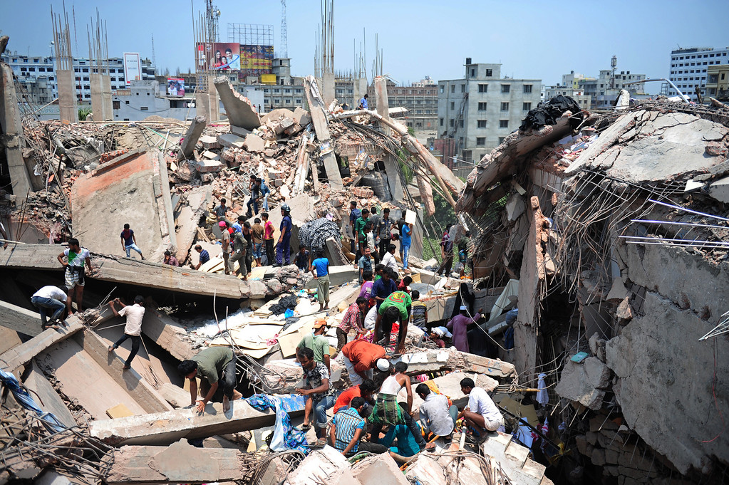 . Bangladeshi civilian volunteers assist in rescue operations after an eight-story building collapsed in Savar, on the outskirts of Dhaka, on April 24, 2013. At least 15 people were killed and many more feared dead when an eight-story building housing a market and garment factory collapsed in Bangladesh on Wednesday, officials said.  AFP PHOTO/Munir uz ZAMAN/AFP/Getty Images