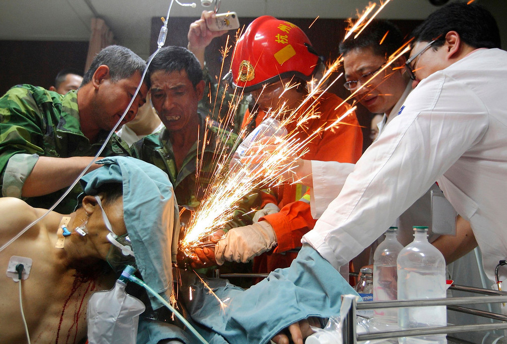 . Fellow workers, a firefighter and doctors work together to cut steel bars which were pierced through a worker\'s body during an operation at a hospital in Hangzhou, Zhejiang province, June 12, 2012. The worker was pierced by seven steel bars during his duty at a bridge construction site on Monday afternoon, local media reported. Picture taken June 12, 2012. REUTERS/China Daily