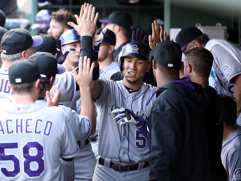 . Carlos Gonzalez #5 of the Colorado Rockies followed by Troy Tulowitzki #2 are congratulated for scoring in the first inning on a hit by Nolan Arenado #28 against the Texas Rangers at Globe Life Park in Arlington on May 7, 2014 in Arlington, Texas.  (Photo by Rick Yeatts/Getty Images)