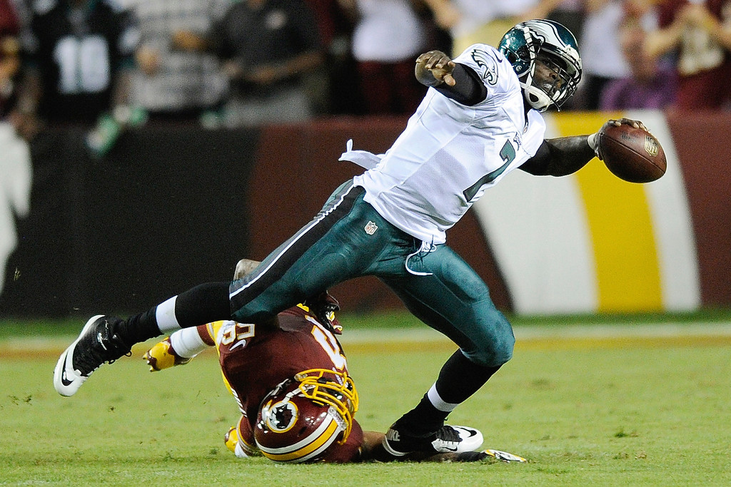 . Philadelphia Eagles quarterback Michael Vick (7) looks for an opening to pass as Washington Redskins inside linebacker Perry Riley gets tangled up in his legs during the first half of an NFL football game in Landover, Md., Monday, Sept. 9, 2013. (AP Photo/Nick Wass)