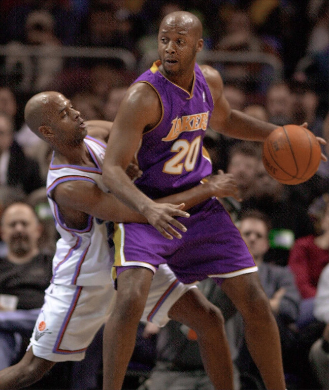 . Lakers guard Brian Shaw, right, keeps the ball away from Cleveland Cavaliers\' guard Bimbo Coles during in January 2001 at Gund Arena in Cleveland.    (DAVID MAXWELL/AFP/Getty Images)