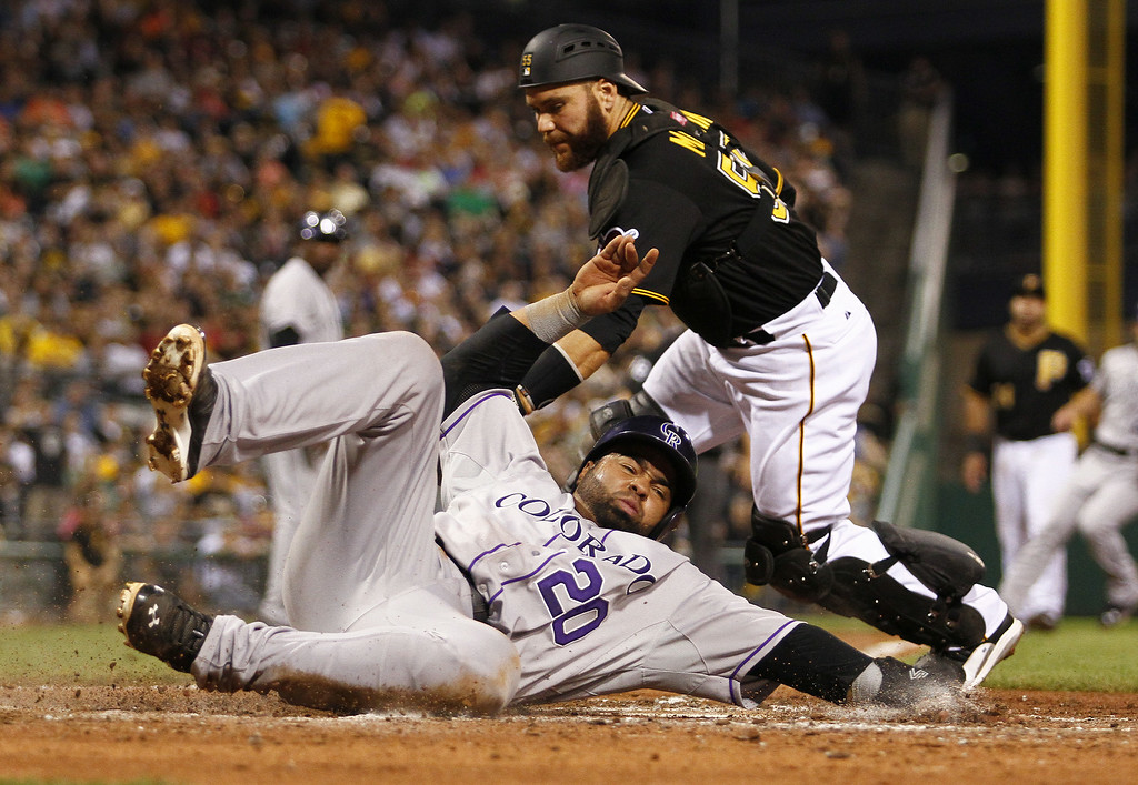 . PITTSBURGH, PA - JULY 18:  Wilin Rosario #20 of the Colorado Rockies score on a RBI single in the sixth inning against Russell Martin #55 of the Pittsburgh Pirates during the game at PNC Park July 18, 2014 in Pittsburgh, Pennsylvania.  (Photo by Justin K. Aller/Getty Images) *** BESTPIX ***