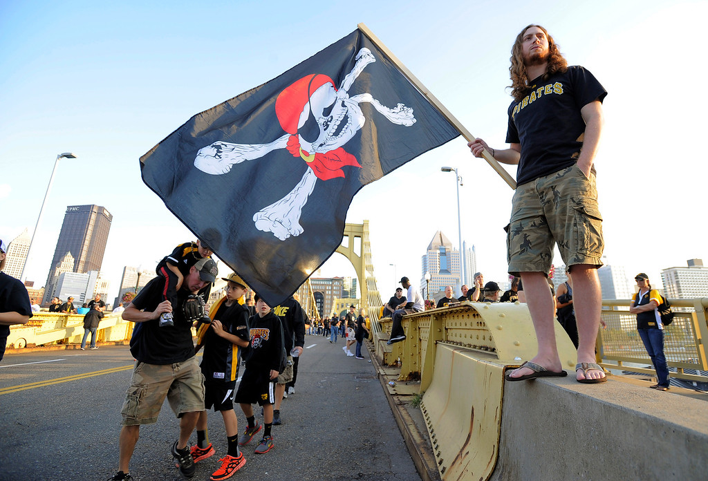 . Derek Buck, of Pittsburgh, waves a Jolly Roger flag as he stands on the Roberto Clemente Bridge as fans make their way to the NL wild-card playoff baseball game between the Pittsburgh Pirates and the Cincinnati Reds on Tuesday, Oct. 1, 2013, in Pittsburgh. (AP Photo/Don Wright)