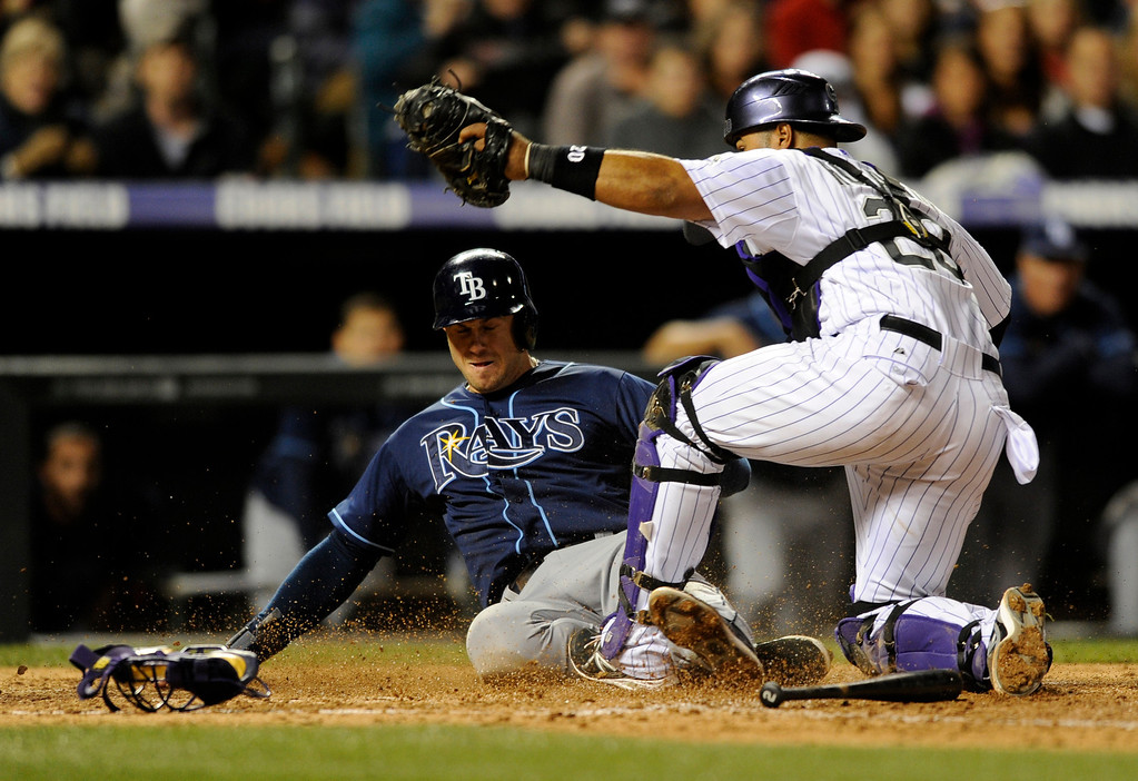 . Tampa Bay Rays\' Evan Longoria, left, is tagged out at home plate by Colorado Rockies catcher Wilin Rosario (20) during the eighth inning of a baseball game on Friday, May 3, 2013, in Denver. (AP Photo/Jack Dempsey)