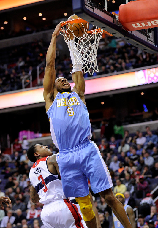 . Denver Nuggets guard Andre Iguodala (9) dunks over Washington Wizards guard Bradley Beal (3) during the first half of an NBA basketball game, Friday, Feb. 22, 2013, in Washington. (AP Photo/Nick Wass)