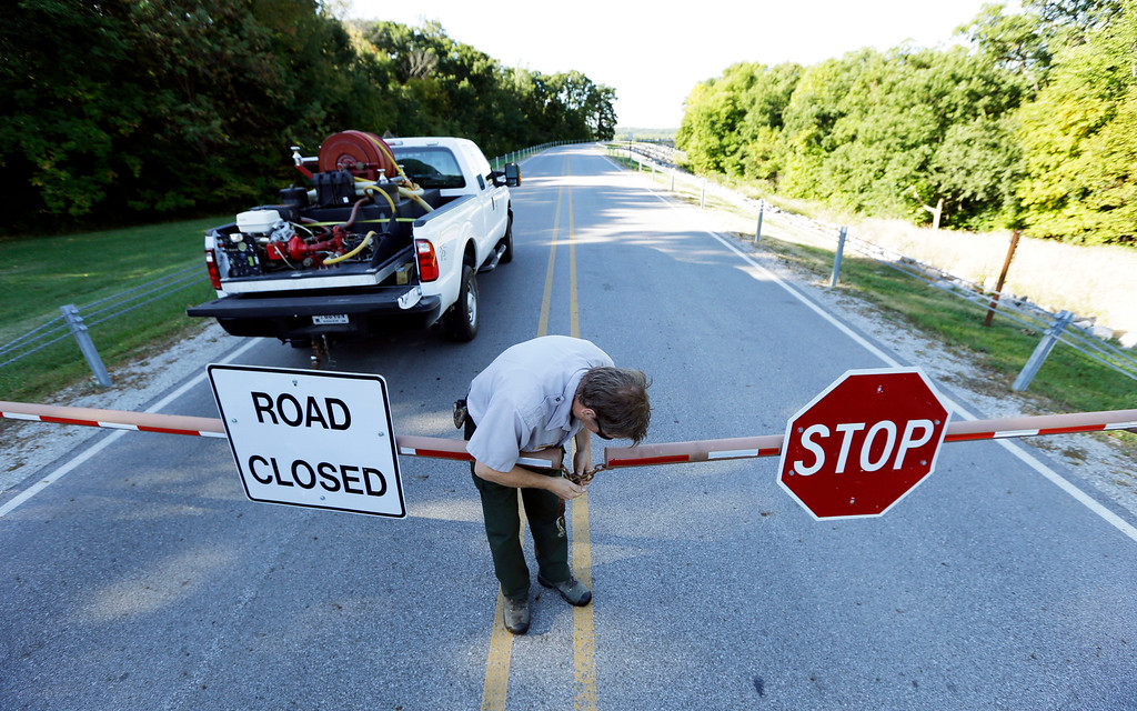 . Park Ranger Scott Rolfes locks a gate closing a road over the dam at Saylorville Lake, Tuesday, Oct. 1, 2013, in Saylorville, Iowa. About 800,000 federal workers are being forced off the job in the first government shutdown in 17 years, suspending most nonessential federal programs and services.(AP Photo/Charlie Neibergall)