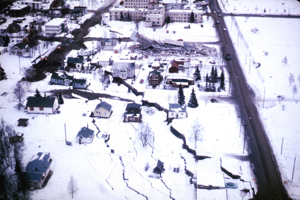 . Alaska Earthquake March 27, 1964. A subsidence trough (or graben) formed at the head of the L Street landslide in Anchorage during the earthquake. The slide block, which is virtually unbroken ground to the left of the graben, moved to the left. The subsidence trough sank 7 to 10 feet in response to 11 feet of horizontal movement of the slide block. A number of houses were undercut or tilted by subsidence of the graben. Note also the collapsed Four Seasons Apartment Building and the undamaged three-story reinforced concrete frame building behind it, which are on the stable block beyond the graben. U.S. Geological Survey photo