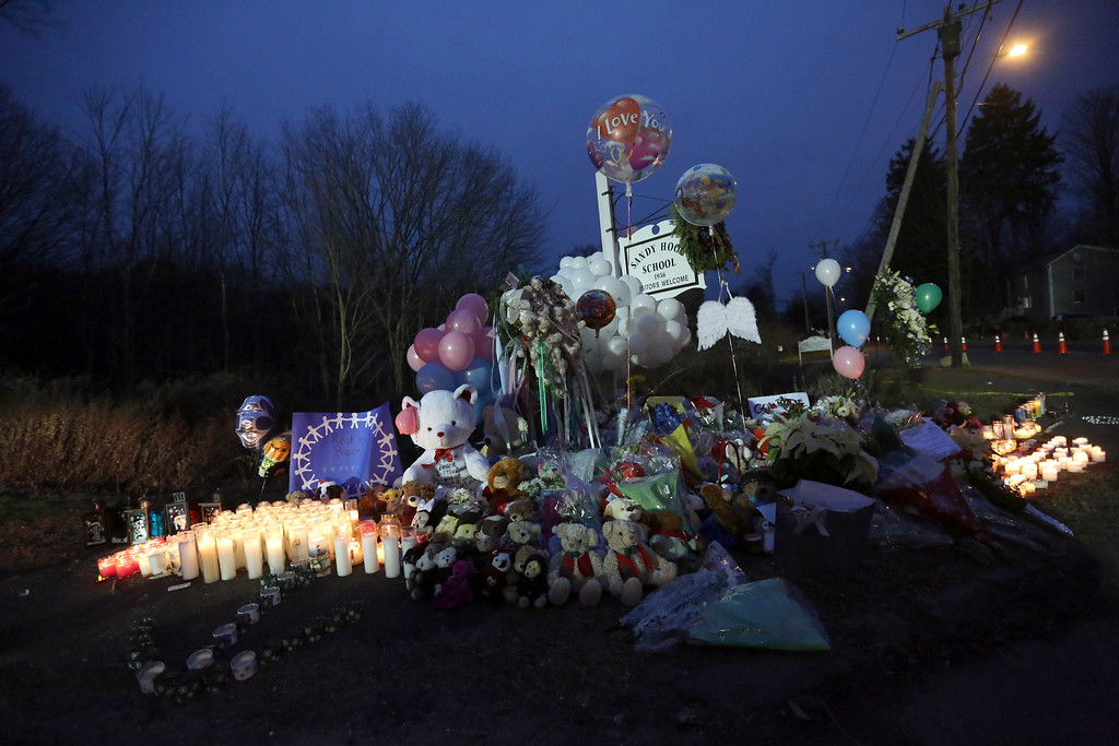 . Candles, balloons, stuffed animals and personal notes are placed on a memorial for the victims of the Sandy Hook Elementary School shooting, Sunday, Dec. 16, 2012, in the Sandy Hook village of Newtown, Conn. A gunman walked into Sandy Hook Elementary School in Newtown Friday and opened fire, killing 26 people, including 20 children. (AP Photo/Mary Altaffer)