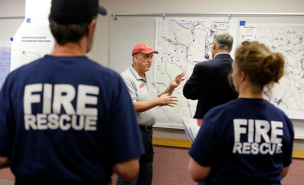 . Fire and rescue personnel look on as Washington Gov. Jay Inslee, center right, is briefed on the Chiwaukum Creek Fire by incident commander Ed Lewis, center left, Friday, July 18, 2014, in Leavenworth, Wash. (AP Photo/Ted S. Warren)