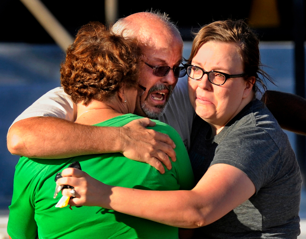 . Tom Sullivan, center, hugs his wife Terry, left, and daughter Megan outside Gateway High School, Friday July 20, 2012, in Aurora. Sullivan is still missing his son, who he said was at the movies where about 50 people were shot 12 fatally early Friday in Aurora. RJ Sangosti, The Denver Post