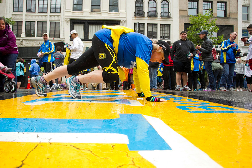 """. A runner does a plank as others cross the finish line after completing the final mile of the Boston Marathon course during \""""#onerun\"""" in Boston, Massachusetts, May 25, 2013.   REUTERS/Dominick Reuter"""