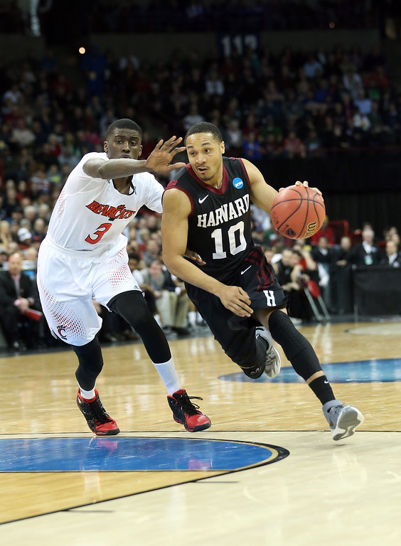 . Brandyn Curry #10 of the Harvard Crimson dribbles past Shaquille Thomas #3 of the Cincinnati Bearcats during the second round of the 2014 NCAA Men\'s Basketball Tournament at Spokane Veterans Memorial Arena on March 20, 2014 in Spokane, Washington.  (Photo by Stephen Dunn/Getty Images)