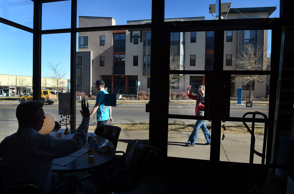 """. Craig Rouse, R Design, waves to a pedestrian from his graphic arts studio at Belmar in Lakewood, CO, January 22, 2013. Rouse says he likes working in a neighborhood setting, \""""we get to know the residents as well as the businesses.\"""" (Photo By Craig F. Walker / The Denver Post)"""